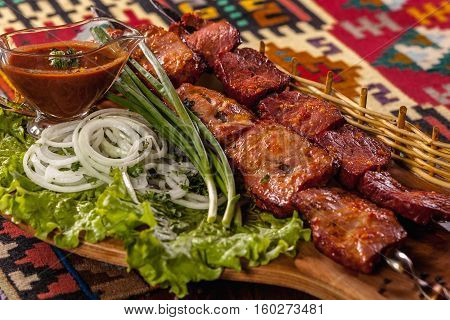 Shashlik, Sauce And Greens On A Wooden Tray