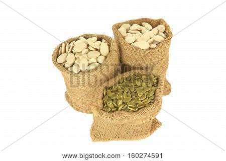 With shell and Hulled (unshelled) Pumpkin seeds in burlap bags (sacks) over white background
