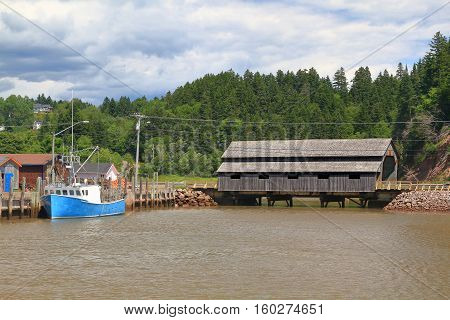 Built in 1935 still in use Covered Wooden Bridge Irish River #1 or Vaughan Creek Bridge St. Martins area New Brunswick part of marina for commercial lobster fishing in moment of high tide