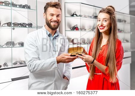 Ophthalmologist giving eyeglasses to the young female client in front of the showcase with eyeglesses in the hospital or store. Happy female customer buying eyeglasses