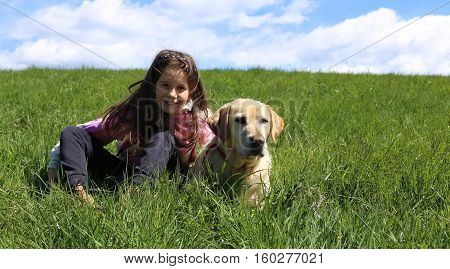 Little Girl And Dog Lying On Green Meadow In The Mountains On A