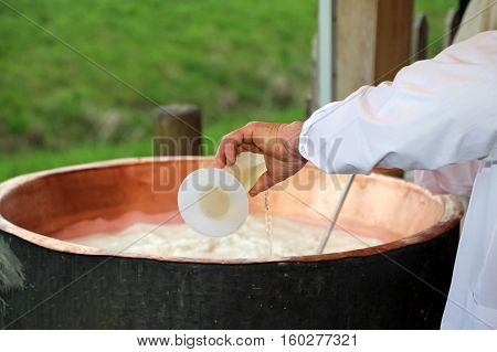 cheesemaker pour rennet into the great copper cauldron to make cheese in the dairy