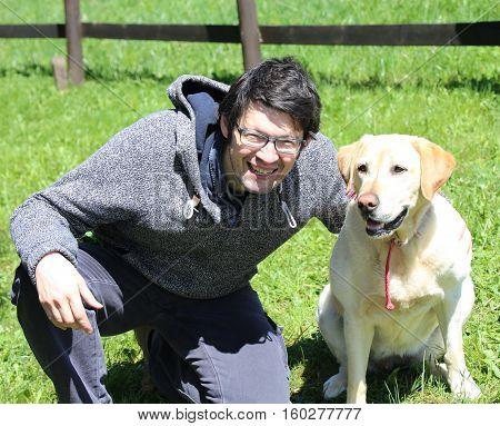 young man with blacks hair with labrador retriever dog