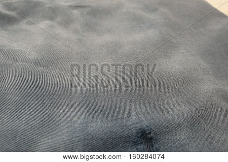 Grey fabric surface with mended hole useful as a background