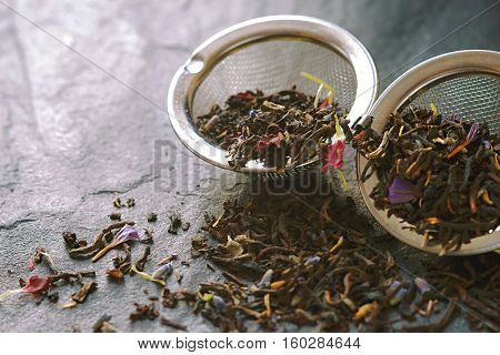 Tea with flower petal in the strainer on the stone background horizontal