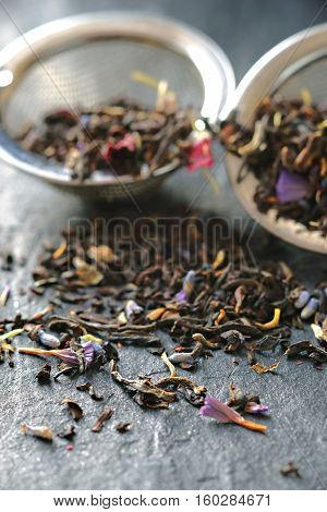 Tea with flower petal in the strainer on the stone background vertical