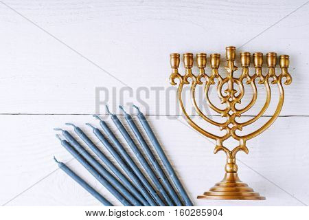Hanukkah menorah and candles on the white wooden table top view