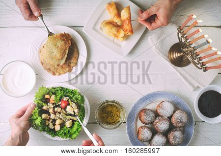 Hanukkah dinner with traditional dishes on the white wooden table