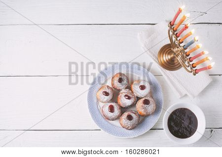 Hanukkah menorah and sufganiot on the white wooden table top view