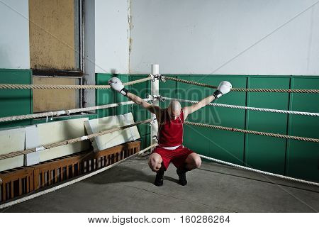 young adult male boxer in red clothes squat and hold the side ropes in the corner of the ring, indoors
