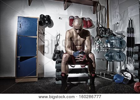 Male boxer full lenght portrait sitting in a changing room looking down holding hands bare chested with a sport equipment behind him