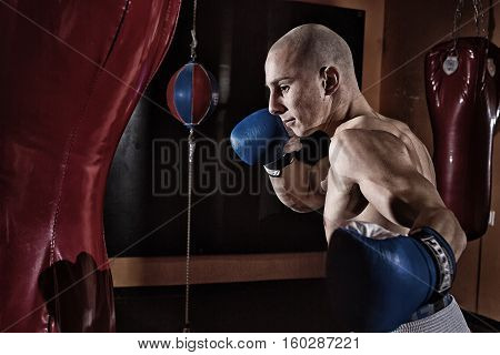 Boxer in a fitness room punching a bag