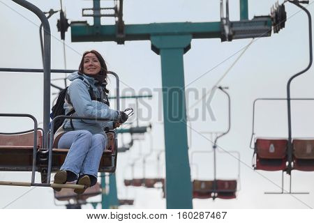 Happy girl in a jacket goes on a chairlift