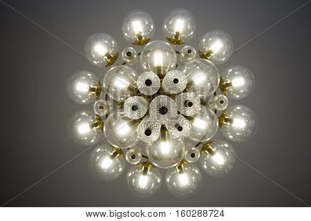 Crystal glass chandelier view from bottom, round shape, round glass bulb covers, lit, energy-efficient light bulbs