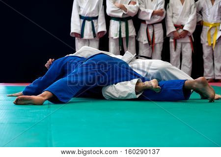 Black belt in Judo immobilizes his opponent to the ground