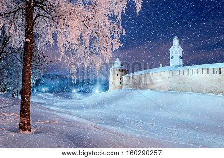 Winter landscape - Novgorod Kremlin in winter night under snowfall in Veliky Novgorod Russia. Winter landscape night view of snowy city Veliky Novgorod - colorful night scene in cold weather