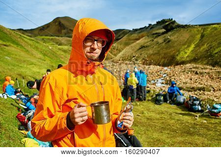 man hiker on the trail in the Islandic mountains. Trek in National Park Landmannalaugar, Iceland. man holding a mug of tea and eating chocolate bar
