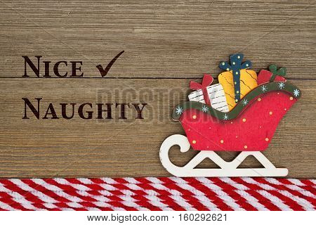 Old fashion Christmas message A retro Christmas sleigh on weathered wood background with text Nice and Naughty
