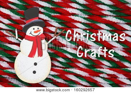 Crafty Christmas message A retro snowman hugging Santa Claus on weathered wood background with text Christmas Crafts