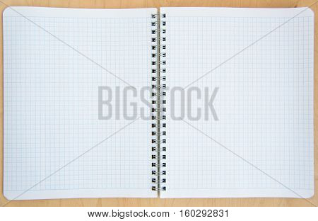 open notebook on a wooden background. Open net note pad with a pen on a gray table
