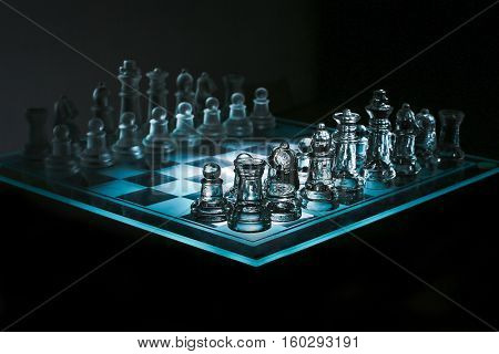 Close up view of a corner of glass transparent chess board with chess pieces on black background