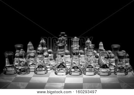 Black and white photo of transparent glass chess board and chess pieces, black background.