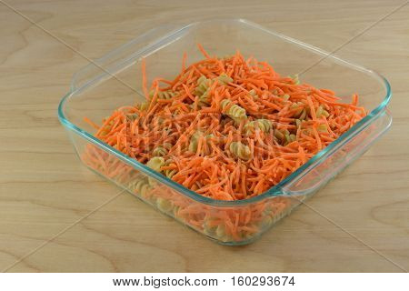 Casserole preparation of raw shredded carrots and cooked whole wheat rotini pasta in glass baking dish