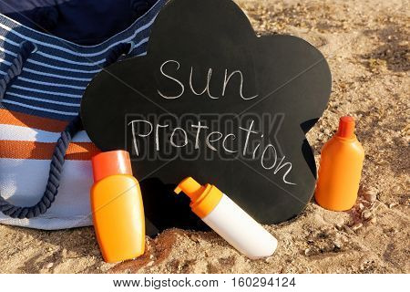 Black board with inscription, beach bag and sunscreen cream on sea coast