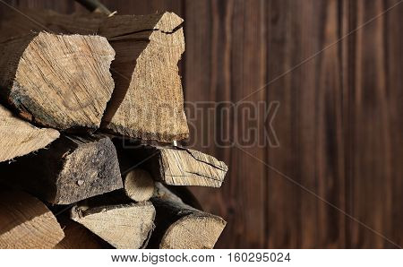 Stack of firewood on blurred background, close up view