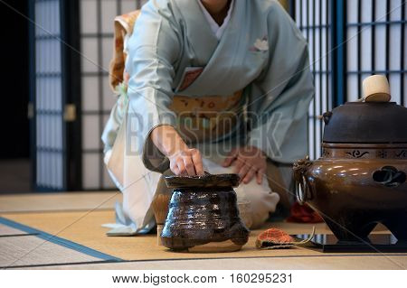 a japanese woman shows the tea ceremony during a public demonstration