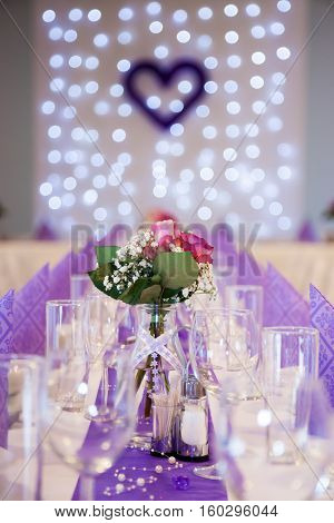 purple wedding table decoration with focus on flower center piece. There are empty water and wine glasses, folded purple decorative paper napkins in two rows, blurred christmas lights and purple decorative heart at the background. Wedding reception table