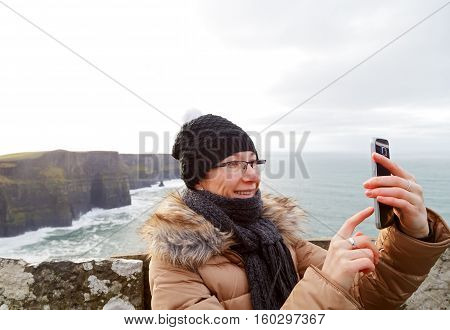 Beautiful woman taking a selfie at cliffs of moher