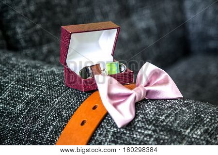 The groom's sophisticated accessories including cuff links in the box leather brown belt and pink bow tie placed on a grey sofa