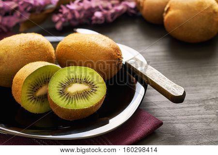 Kiwifruit served on plate on black wooden background