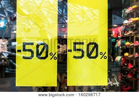 sale sign on cloth store. Sticker sign - Sale up to half-price 50 percent on store window with clothes during winter sale season time