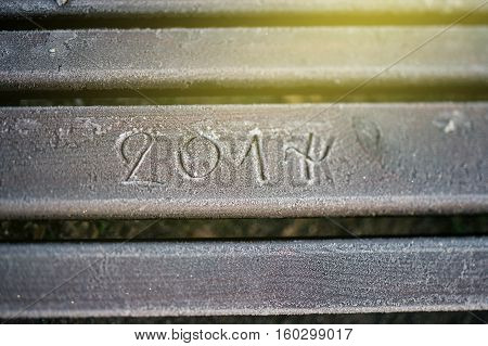 2017 numbers written on a covered with snow and frost park bench during a cold morning