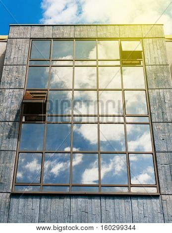 Sunny flare over abstract glass-concrete facade of a modern building covered in reflective plate glass with clouds refletetions