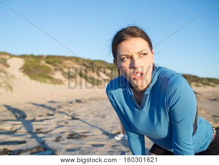 Young active girl jogger on beach taking breath