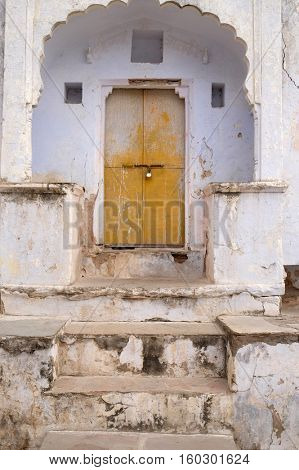 PUSHKAR, INDIA - FEBRUARY 18: Decrepit door in an old house in Pushkar, India on February 18, 2016.
