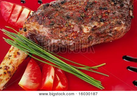 savory plate : roasted meat shoulder on red plate with chives and tomato isolated on white