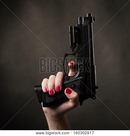 Pistol in female arm on black background