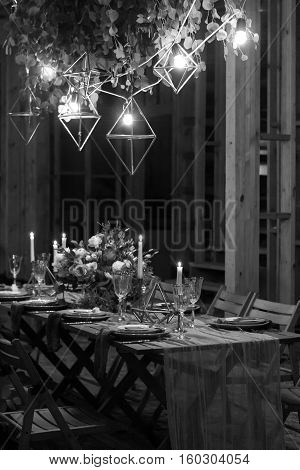 Decoration festive table before a banquet. Above the table garland with the lamps. Black and white.