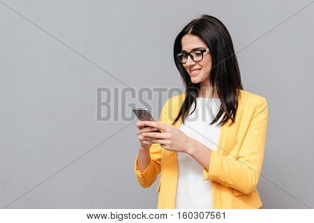 Cheerful woman wearing eyeglasses and dressed in yellow jacket chatting by her phone over grey background. Look at phone.
