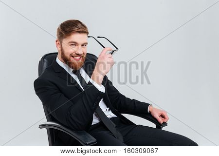 Smiling bearded business man in black suit pull off glasses and looking at camera as well as sitting on armchair. Isolated gray background