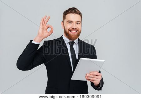 Young bearded business man in black suit holding tablet computer and showing ok sign as well as looking at camera. Isolated gray background