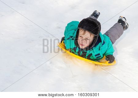 Boy sliding down the hill on saucer sleds outdoors winter day ride down the hills winter games and fun
