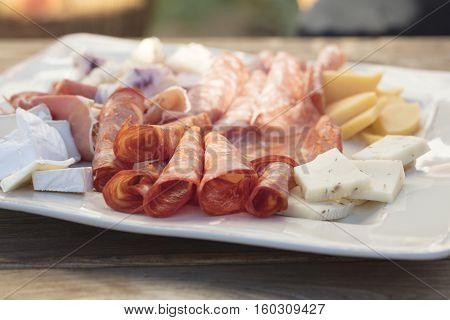 A plate of salami sopressata pepperoni cheddar and brie cheeses for an outdoor get together