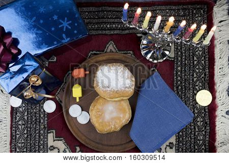 Hanukkah Menorah with lit Candles Gifts Dreidels and Jelly Filled Pastries served on a wooden plate for the Holiday