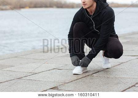 Closeup of attractive young man tying shoelaces before running outdoors