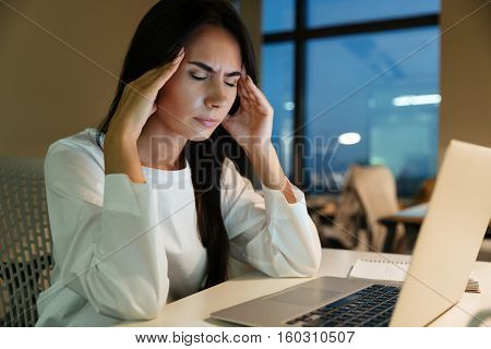Tired fatigued young businesswoman touching her temples and having headache in office